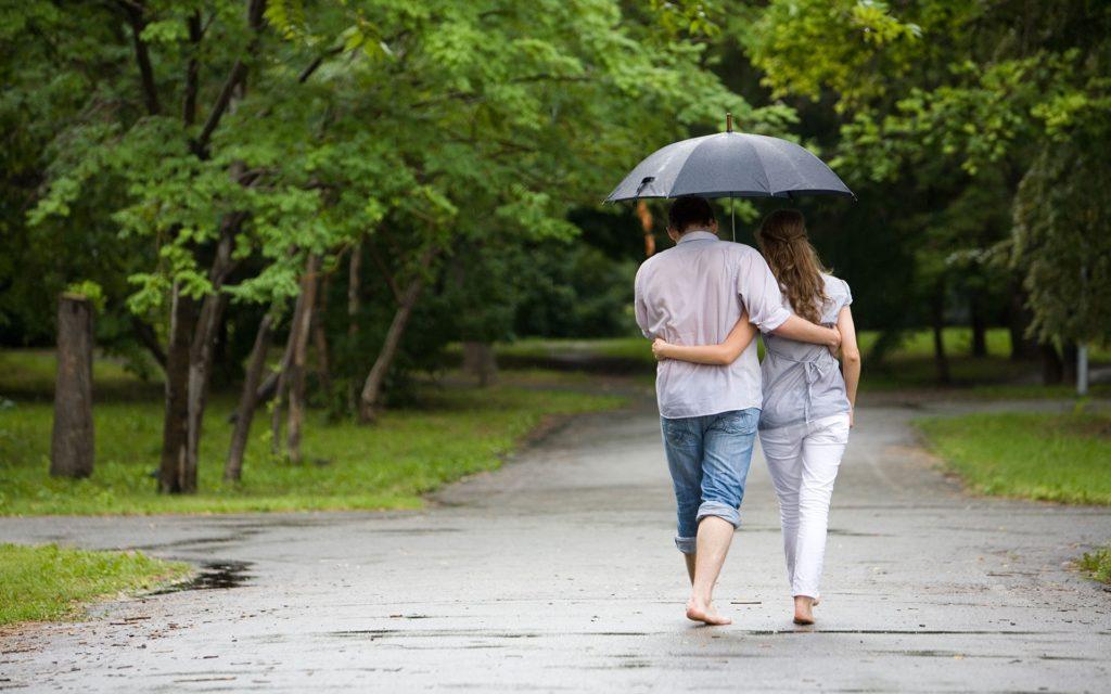 Мужчина и девушка гуляют под зонтом