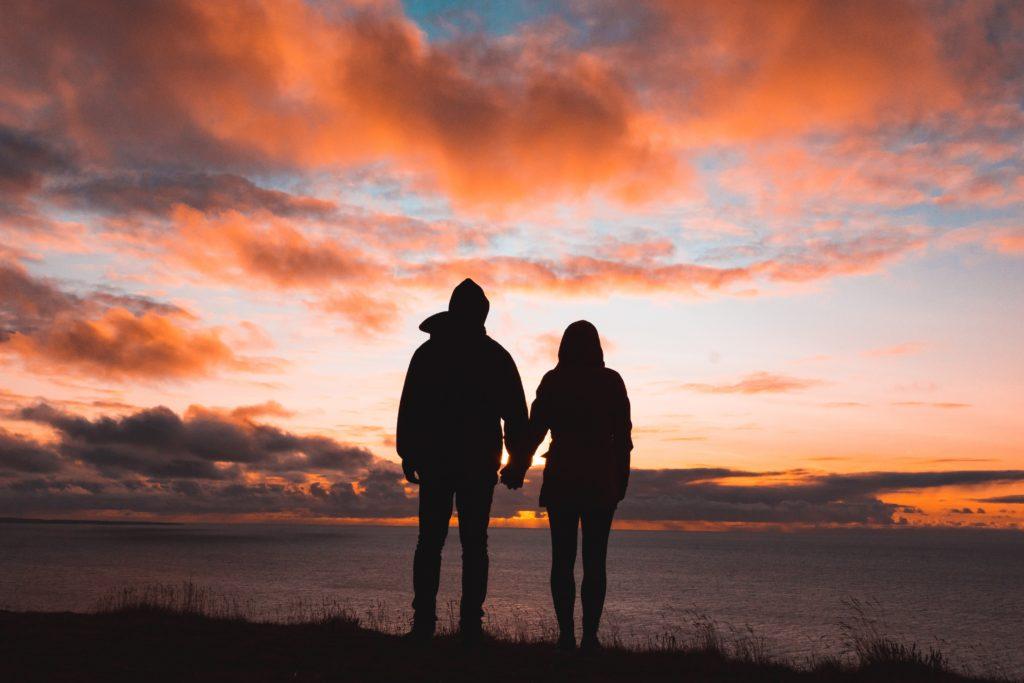 Любящая пара смотрят на закат